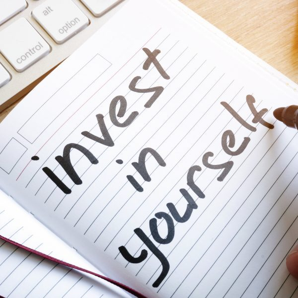Man is writing invest in yourself in a note.